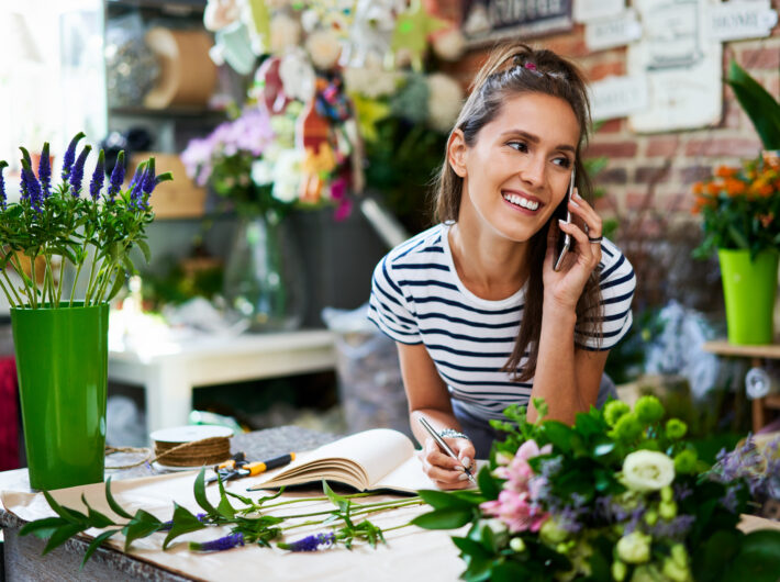 Cheerful florist on phone with client and writing down their order